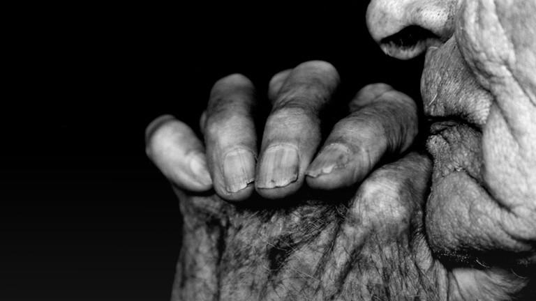 Die Hand und das Gesicht einer alten Person.
