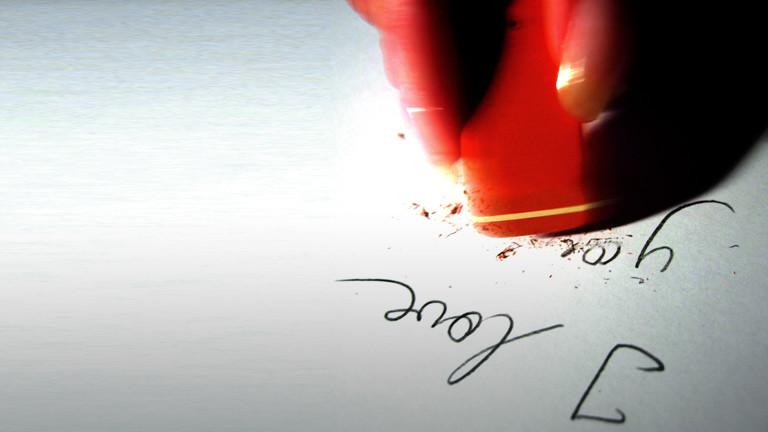 """Jemand radiert mit einem Radiergummi die Wörter """"I love you"""" aus."""