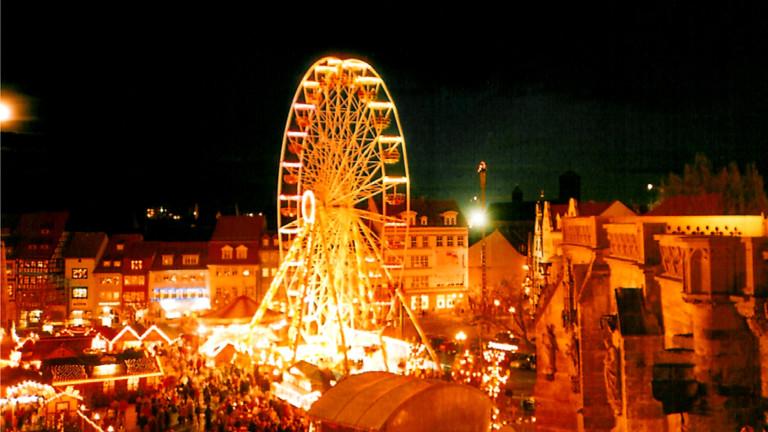 Weihnachtsmarkt bei Nacht mit Riesenrad.