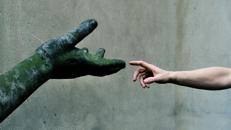 Menschliche Hand trifft Statuen-Hand