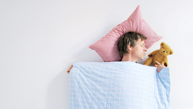 Ein Mann schläft mit Teddy im Arm