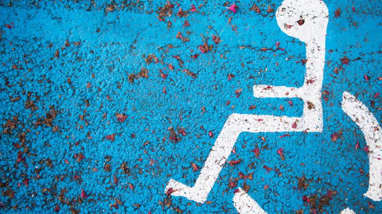 Rollstuhlfahrer-Symbol auf Asphalt.