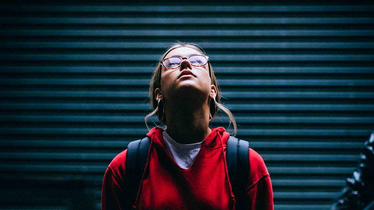 Junge Frau mit Brill schaut in die Luft