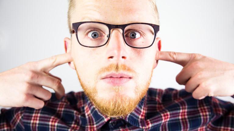 Junger Mann hält sich mit entsetztem Gesichtsausdruck die Ohren zu