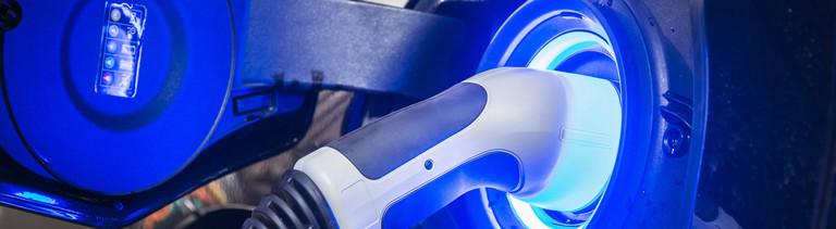 Blau leuchtende Ladesteckdose an einem E-Auto