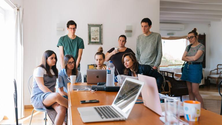 Junge Menschen schauen gemeinsam auf einem Laptop während eines Meetings.