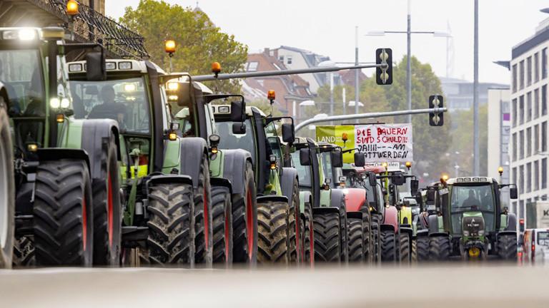 Landwirte fahren mit Traktoren bei einer Demonstration durch eine Innenstadt.