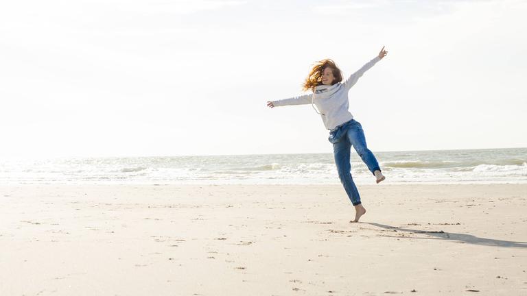 Eine Frau hüpft alleine glücklich über den Strand.