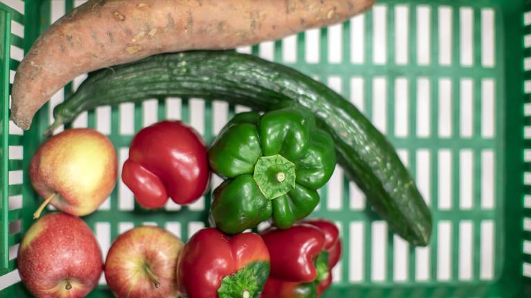 Krummes Obst und Gemüse liegt in einer Kiste.