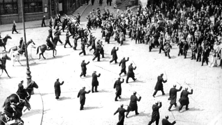 Polizisten mit erhobenen Schlagstöcken sowie berittene Polizei steht während der Unruhen in Berlin im Jahr 1919 einer demonstrierenden Menschenmenge gegenüber.