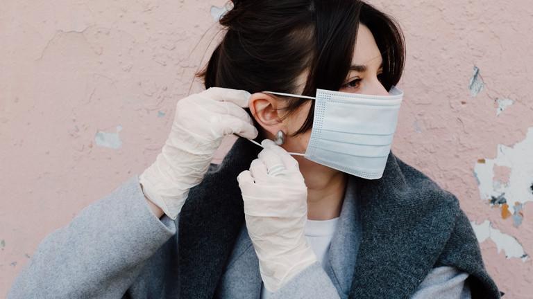 Eine Frau setzt sich eine Maske auf.