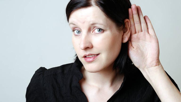 Eine Frau hält sich zum Lauschen die Hand ans Ohr.