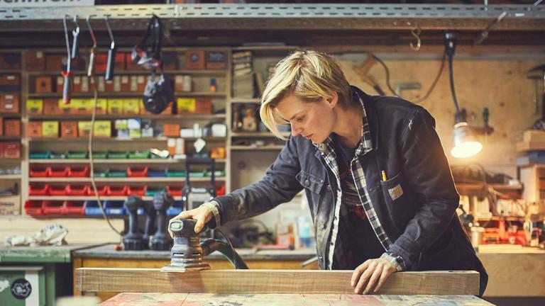 Eine Frau schleift mit einer Maschine ein Stück Holz.