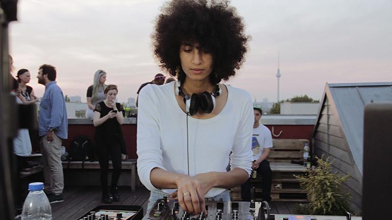 Eine Frau steht an einem DJ-Pult, im Hintergrund ist der Berliner Fernsehturm.