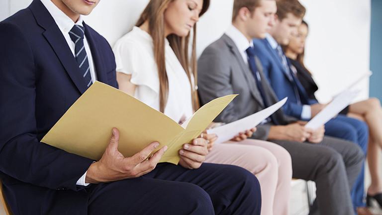 Junge Menschen sitzen in Businesskleidung auf einer Bank und haben Bewerbungsunterlagen in der Hand.