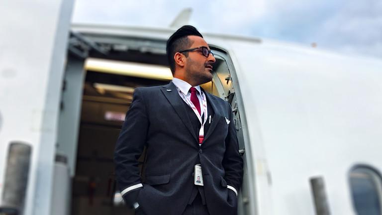Ein Mann steht in einer Uniform im Eingang eines Flugzeugs.