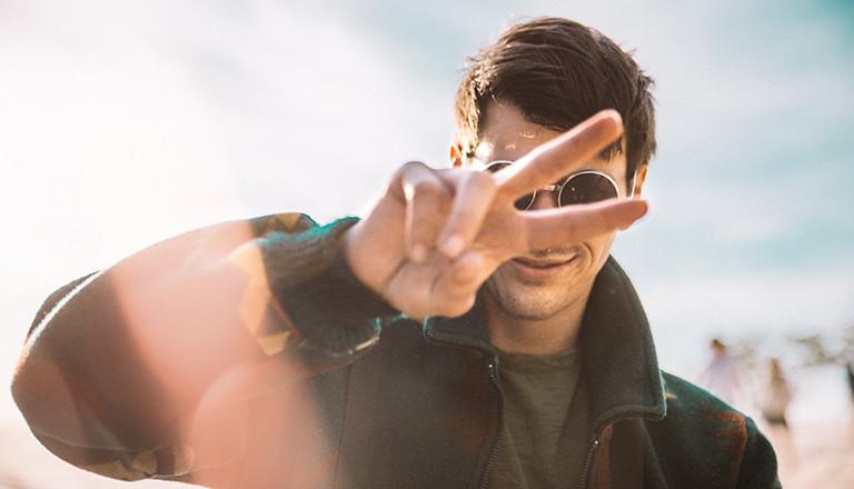 Ein Mann mit Sonnenbrille zeigt mit seinen Fingern das Peace-Zeichen.