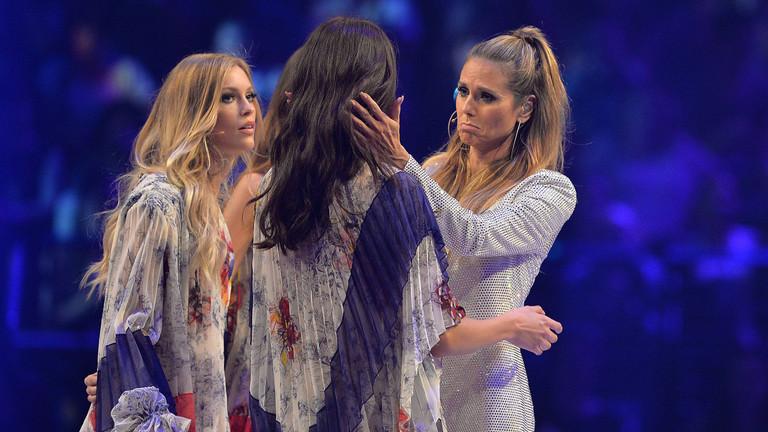 Heidi Klum steht auf einer Bühne und umarmt eine Kandidatin von Germany's Next Topmodel.