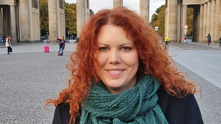 Portrait von Nina Käsehage vor dem Brandenburger Tor in Berlin