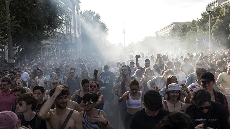 Eine Menschenmenge feiert auf der Straße und im Hintergrund steht der Berliner Fernsehturm.