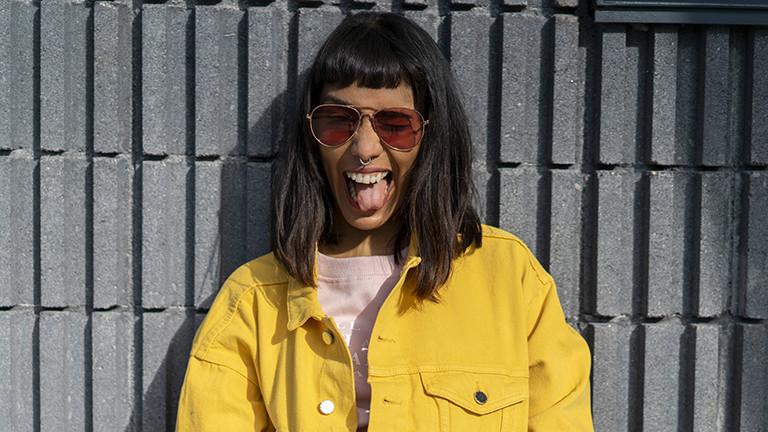 Eine Frau mit Sonnenbrille streckt die Zunge raus und lacht.