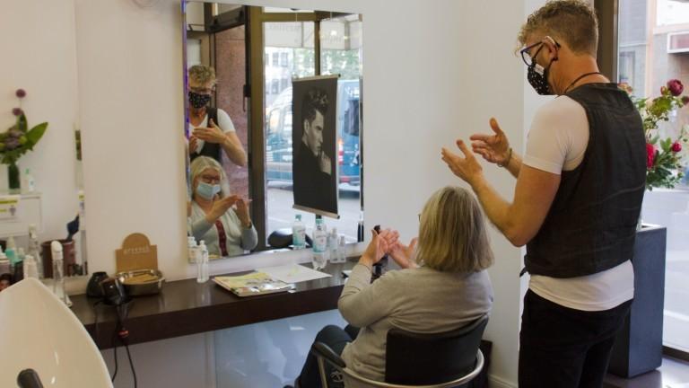 Der gehörlose Friseur Ralph unterhält sich per Gebärdensprache mit einer Kundin