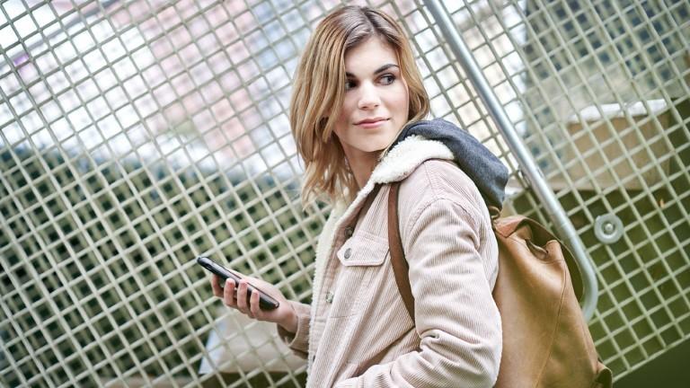 Eine junge Frau mit ihrem Handy in der Hand