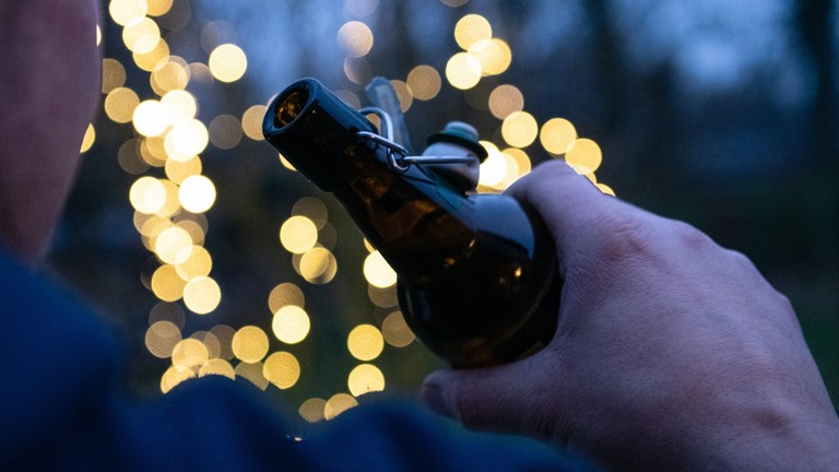 Ein Mann hält eine Flasche mit Bier in der Hand (gestellte Szene).