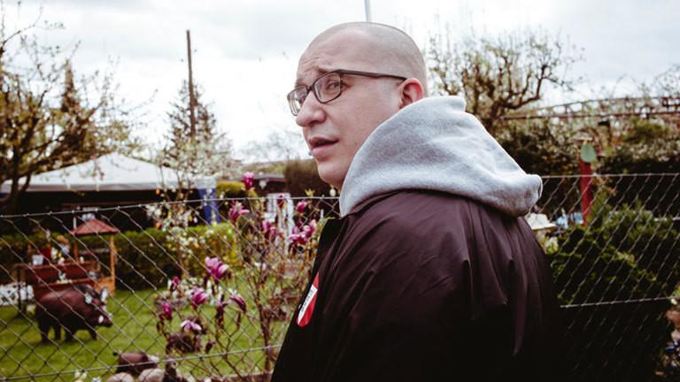 Rapper Audii88 vor einem Gartenzaun