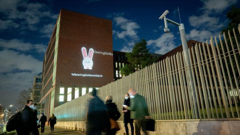 """Ein Hase wird auf die Fassade der Zentrale des Bundesnachrichtendienstes (BND) projiziert. Unter dem Hasen ist die Internetadresse """"followtheglitchkarnickel.de"""" zu sehen"""