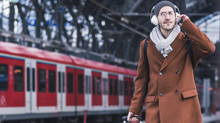 Mann mit Kopfhörern und Koffer am Bahnsteig.