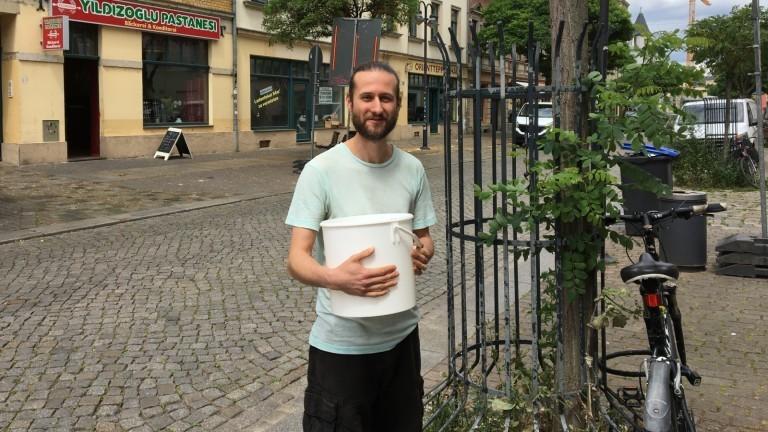 Sven Wruck steht mit einem Eimer vor einem Baum, den er gießen will