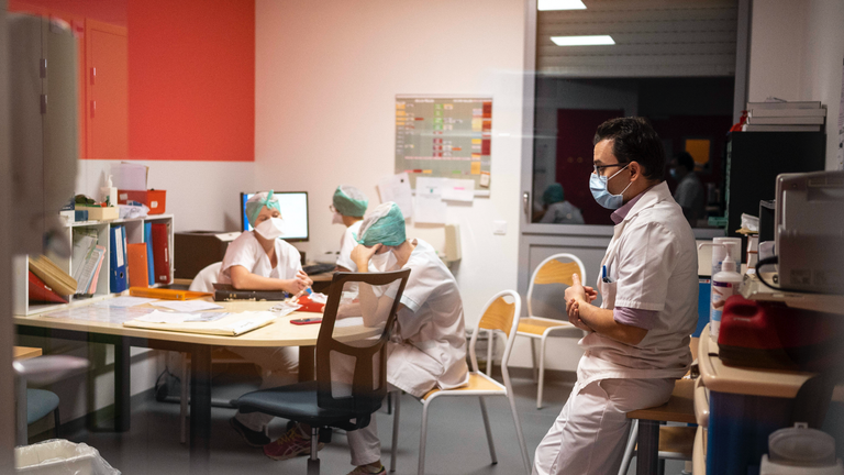 Ein Arzt und mehrere Krankenschwestern sitzen erschöpft in einem Aufenthaltsraum