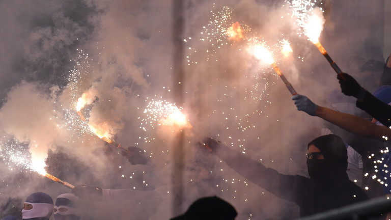 Fans halten Pyrotechnik in der Fankurve in die Luft.