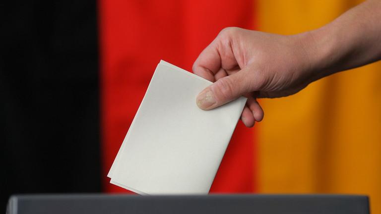Eine Hand steckt einen Wahlzettel in eine Wahlurne vor einer Deutschlandflagge.