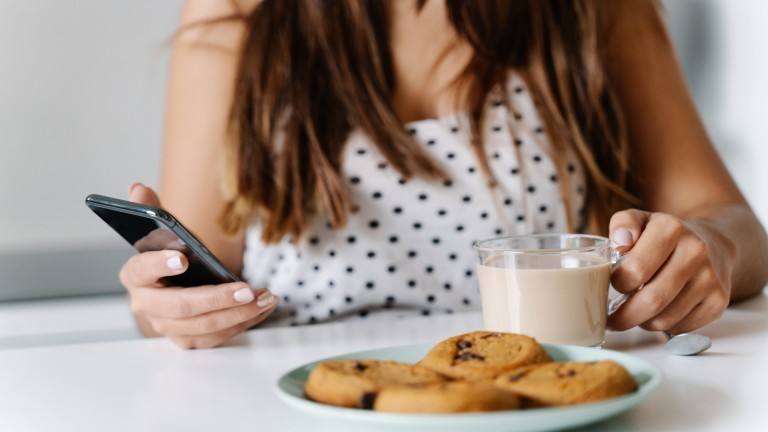 Cropped anonymous brunette woman sitting at table and surfing on mobile phone while drinking coffee with milk at modern kitchen.