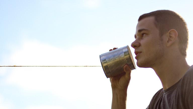 Ein Mann spricht in ein Dosentelefon