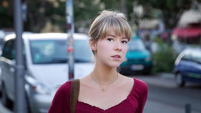 Blonde Frau in rotem Oberteil an einer Straße