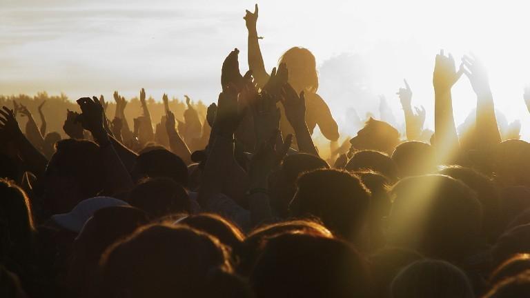 Eine feiernde Festivalmenge im Sonnenuntergang.