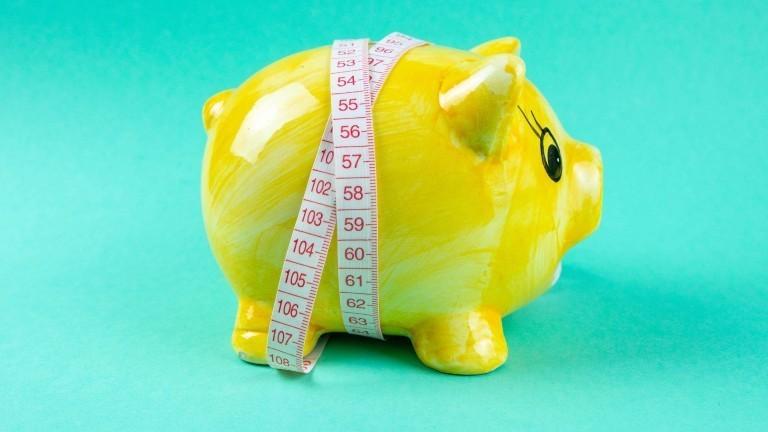 Ein gelbes Schwein mit einem Maßband um den Bauch.