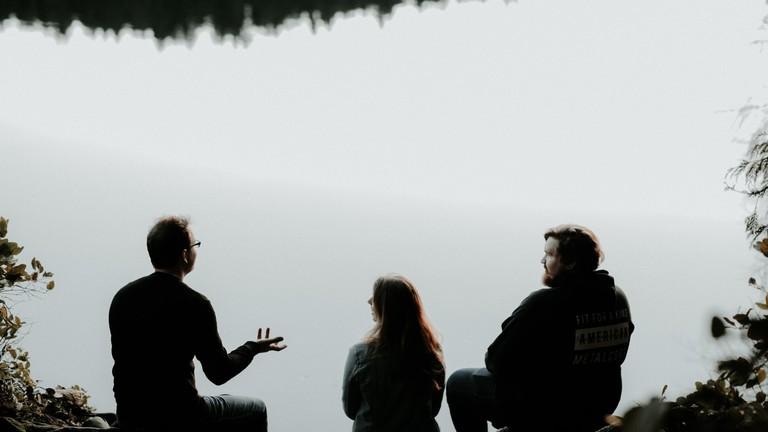 Drei Menschen unterhalten sich an einem See