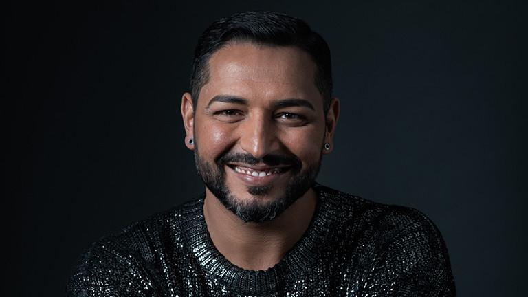 Ein Mann mit dunklen Haaren und Bart, der lächelt