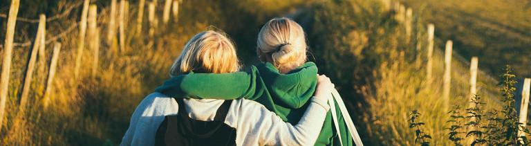 Zwei Frauen legen sich den Arm um die Schulter