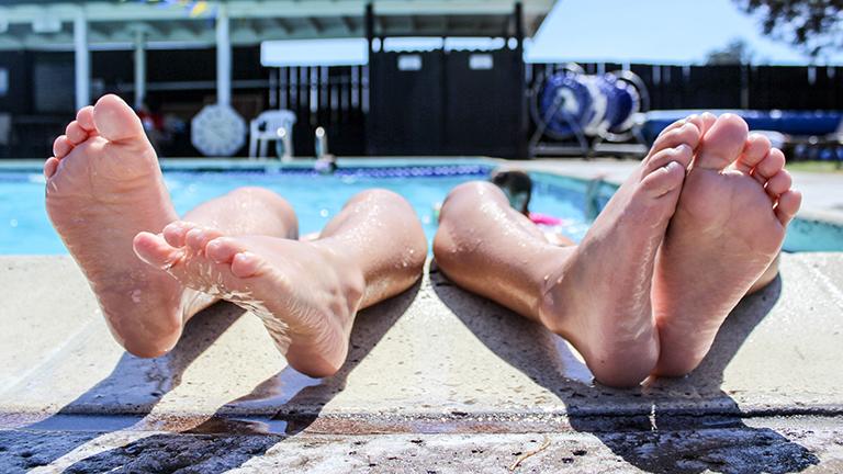 Zwei Paar Füße am Rand eines Pools