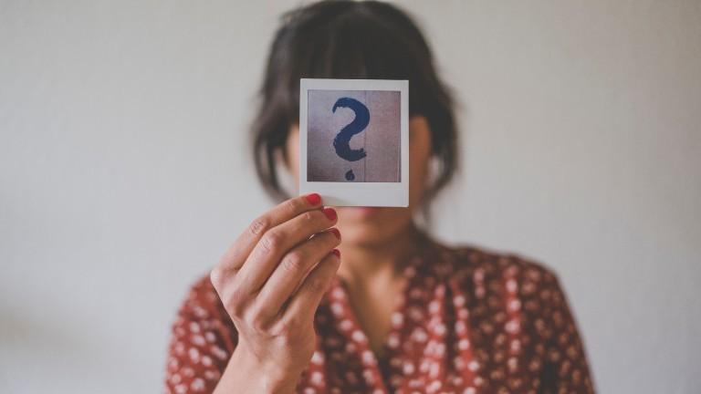Frau hält sich ein Polaroid mit einem Fragezeichen darauf vor das Gesicht.