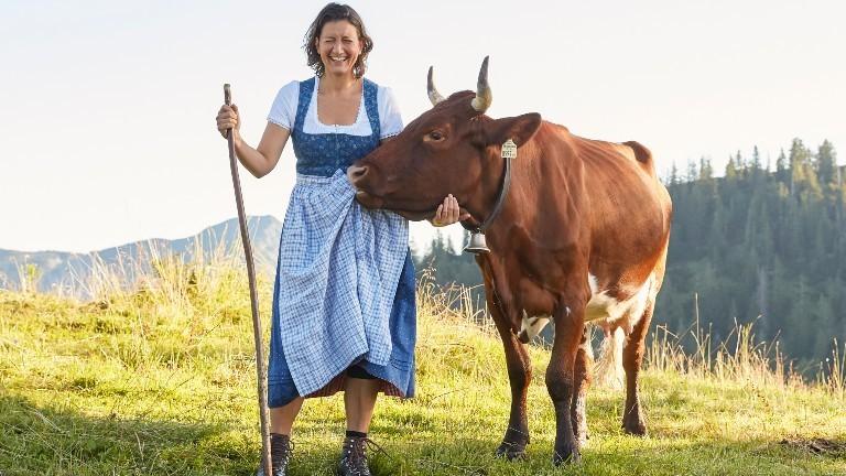 Julia Barbarino steht auf der Alm und eine Kuh beisst ihr in die Schürze
