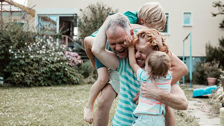 Zwei Männer, die mit zwei Kindern im Garten spielen