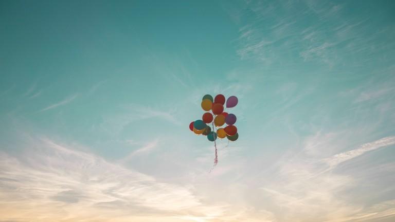 Luftballons fliegen am Himmel.