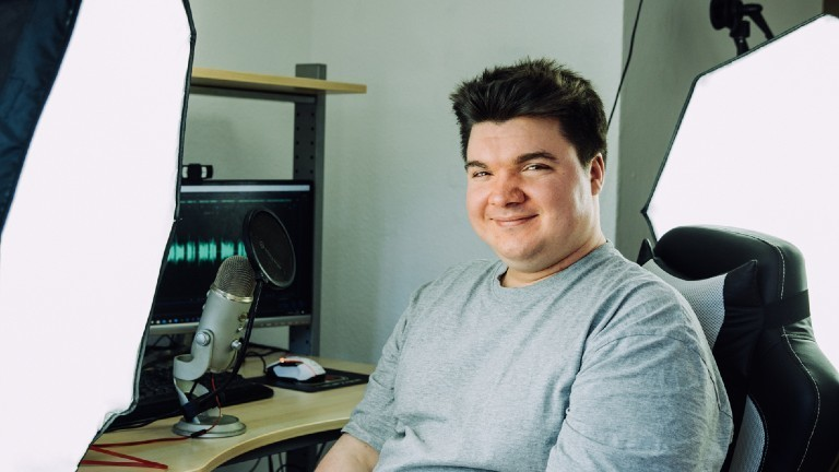 Lukas Krämer vor seinem Mikrofon und Laptop
