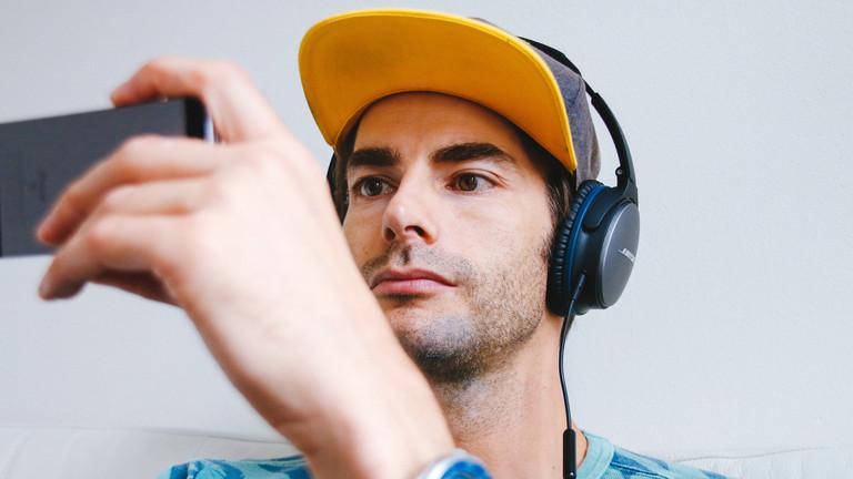 Mann mit Smartphone und Kopfhörern